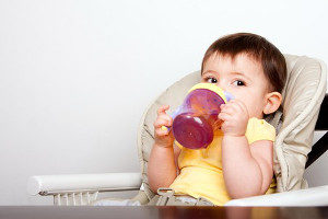 infant drinking from a sippy cup