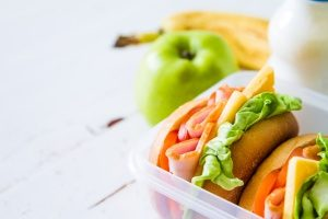 two sandwiches packed in bento lunch boxes alongside a banana and an apple