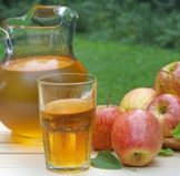 apples set down next to a pitcher and glass of apple juice, one of the most healthy alternatives to soda