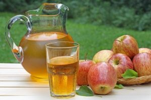 apples set down next to a pitcher and glass of apple juice one of the juice is a good alternative to sodas