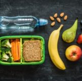 nice healthy lunch including a wide array of fruits as well as brocolli carrots and a sandwich inside of a bento lunch box and a water bottle