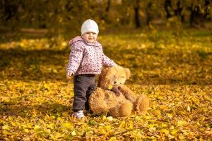 small child outside in a pile of leaves, demonstrating one of the most fun activities for your kids