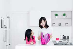 Mother packing her childs lunch in a bento lunch box