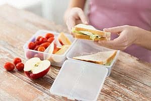 apples and a sandwich inside a plastic lunch box that is not considered one of the safer BPA-free lunch boxes that most parents use for their children
