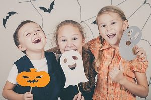 Children holding up cut out masks for halloween