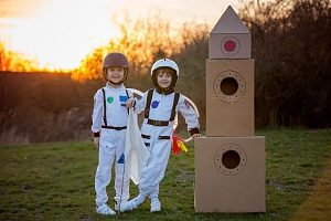 kids in a home made astronaut costume next to a cardboard rocket ship