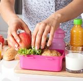 woman preparing food for her and her daughters who both have bento lunch boxes