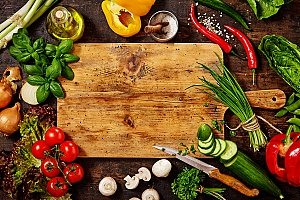 a cutting board with fresh vegetables that will be stored in a bento lunch box for a kid to take to school