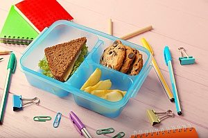 a lunch that contains a sandwich and apple slices as well as cookies that can be easily stored in bento lunch boxes