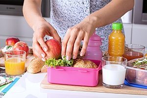 bento lunch boxes being used by a mother who is packing a healthy lunch for her kids in a BPA free lunch box