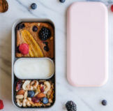 Banana wholemeal bread with mixed nuts and berries and yogurts packed in a bento lunch box