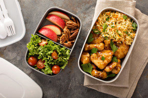 Chicken and rice in bento lunch box next to a side salad and apple bento lunch box