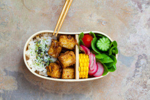 Crispy tofu and rice with veggies in an insulated bento box