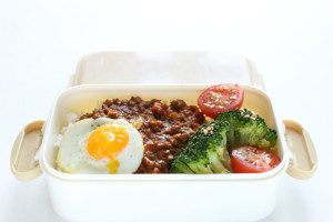 Quail egg and ground beef with veggies in bento lunch box for adults