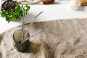 eco-friendly stainless steel drinking straws in a cup on a white table