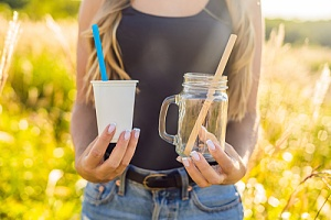 girl holding plastic cup and straw in one hand and a bamboo biodegradable cup and straw in the other hand