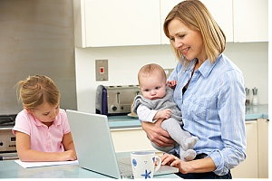 Mom holding baby as she blogs