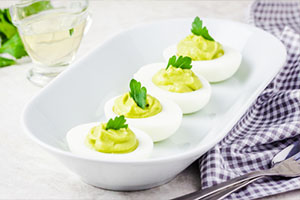 Avocado devilled eggs with parsley on white background