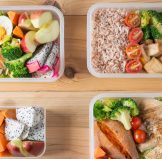 four bento lunch boxes with food in them for lunch