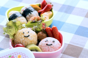 a bento box lunch with rice and lettuce