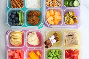 four colorful bento lunch boxes shown with healthy meals inside of them