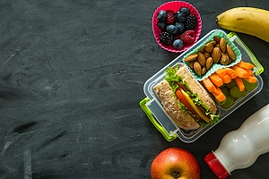 lunch in a bento lunch box with fruits and vegetables around it