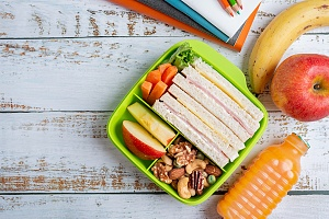 sandwich in a bento lunch box with apples and other vegetables