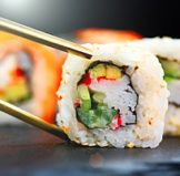 a sushi roll that is being prepared for a bento lunch box