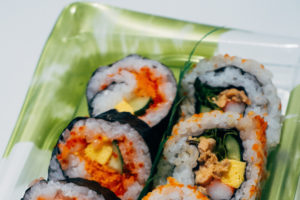bento box contains sliced sushi rolls