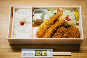 traditional wooden bento box contains rice and other food