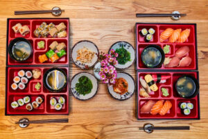 bento lunch boxes with chopsticks to the side contain sushi and other miniature food